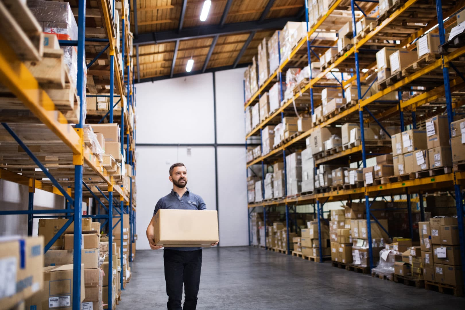 Young male warehouse worker or a supervisor walking with a large box.